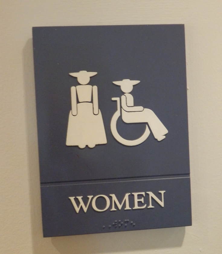 Colonial Williamsburg ladies room sign with figures wearing in colonial dresses