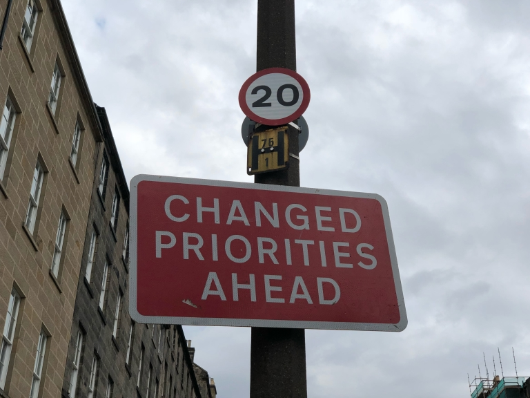 Changed priorities ahead road sign